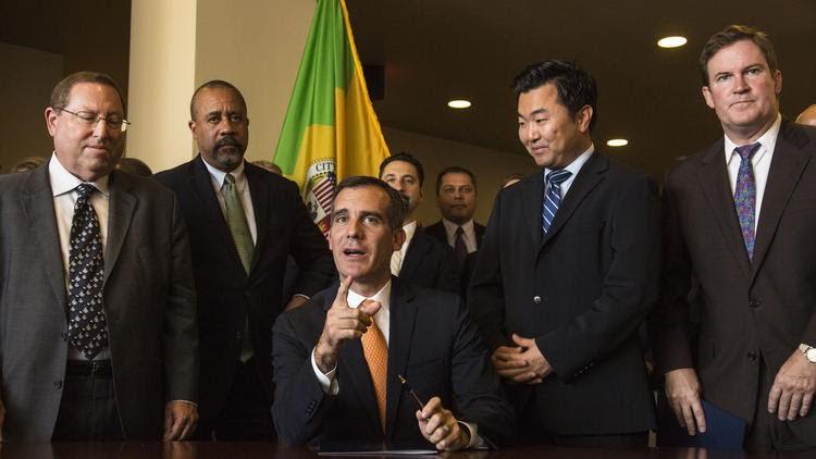 Los Angeles Mayor Eric Garcetti (sitting) speaks to reporters as Councilman David Ryu (right) listens. (Courtesy of David Ryu staff)