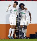 Augsburg's Ji Dong-won, left, celebrates with teammate Caiuby after scoring his side's third goal during the Europa League Group L soccer match between FC Augsburg and AZ Alkmaar at the WWK Arena in Augsburg, southern Germany, Thursday Nov. 5, 2015. (AP Photo/Matthias Schrader)