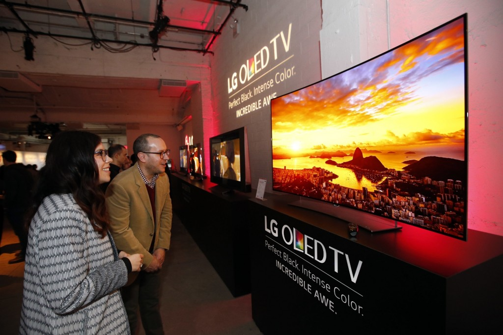 Attendees marvel at an LG Curved 4K UHD OLED TV (Model 65EG9600) at LG and Netflix's Dare to See OLED event in New York. (Photo by Jason DeCrow/Invision for LG Electronics/AP Images)