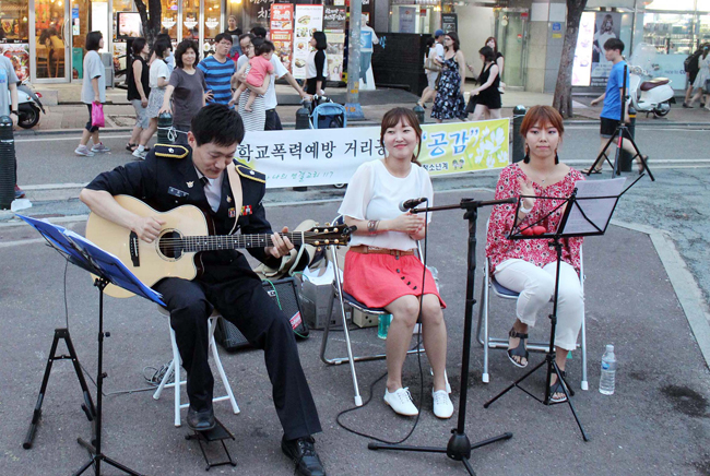 Police lieutenant Song Jun-han plays the guitar on a street near Hongik University, Seoul. (Yonhap)