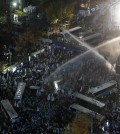 South Korean riot police officers spray water cannons as police officers try to break up protesters trying to march to the Presidential House after a rally against government's policy in Seoul, South Korea, Saturday, Nov. 14, 2015. Police fired tear gas and water cannons Saturday as they clashed with anti-government demonstrators who marched through Seoul in what was believed to be the largest protest in South Korea's capital in more than seven years.(AP Photo/Ahn Young-joon)