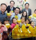 "Members of the Oriental Mission Church in Los Angeles with ""always thankful"" coinbanks (Park Sang-hyuk/Korea Times)"