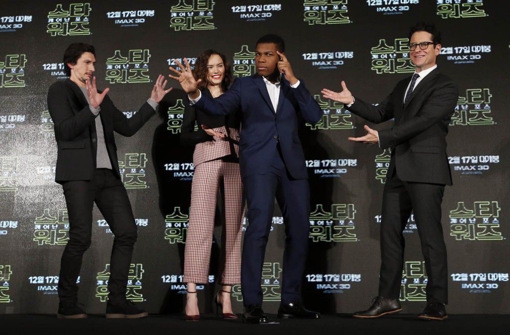 """Actor Adam Driver, left, actress Daisy Ridley, second from left, actor John Boyega, second from right, and director J.J. Abrams pose for the media during a press conference for their new movie """"Star Wars: The Force Awakens,"""" in Seoul, South Korea, Wednesday, Dec. 9, 2015. The movie is to be released in South Korea on Dec. 17. (AP Photo/Lee Jin-man)"""