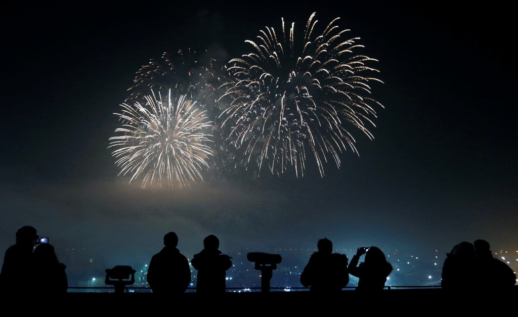 People watch and use their smartphones to take picture of fireworks, to celebrate the New Year at the Imjingak Pavilion near the border village of Panmunjom in Paju, South Korea, Friday, Jan. 1, 2016. (AP Photo/Lee Jin-man)