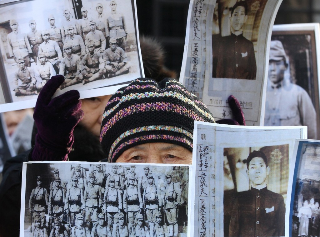 A South Korean bereaved family member of victims of World War II attends a rally demanding full compensation and apology from Japanese government in front of Foreign Ministry in Seoul, South Korea, Monday, Dec. 28, 2015. The foreign ministers of South Korea and Japan will meet Monday to try to resolve a decades-long impasse over Korean women forced into Japanese military-run brothels during World War II. (AP Photo/Ahn Young-joon)
