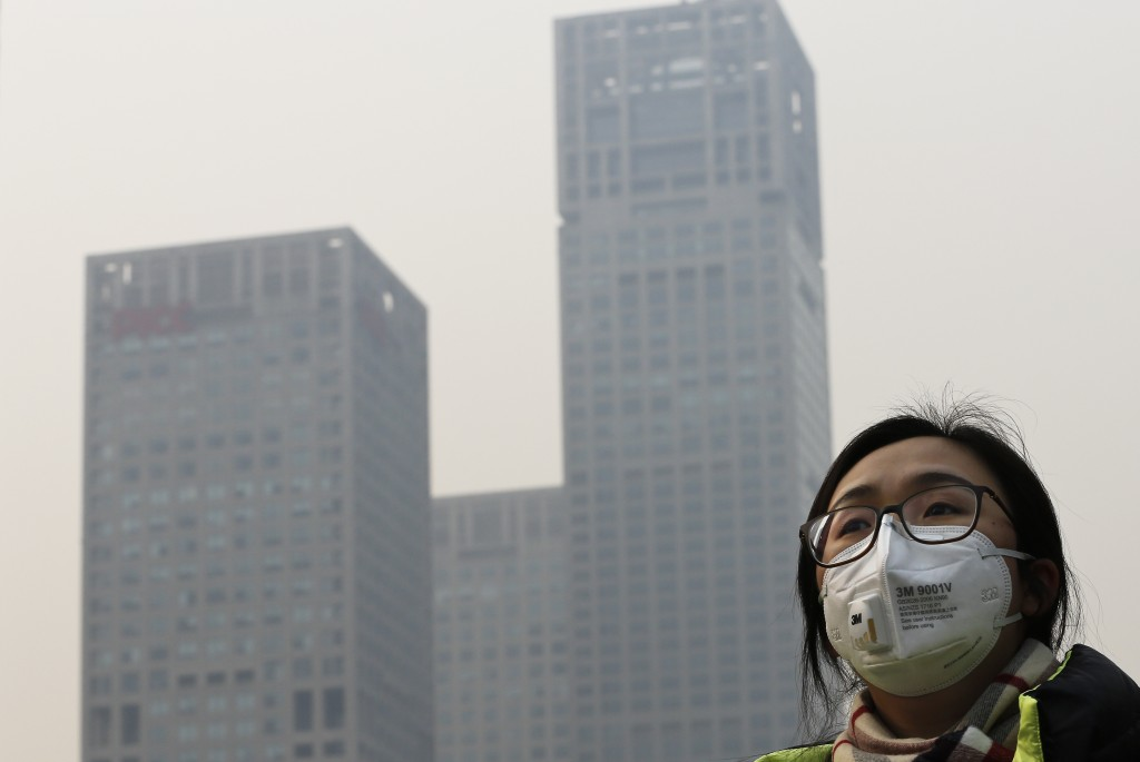 A woman wearing a face mask to protect herself from pollutants walks past office buildings shrouded with pollution haze in Beijing, Monday, Dec. 7, 2015. Beijing issued its first-ever red alert for smog on Monday, urging schools to close and invoking restrictions on factories and traffic that will keep half of the city's vehicles off the roads. (AP Photo/Andy Wong)