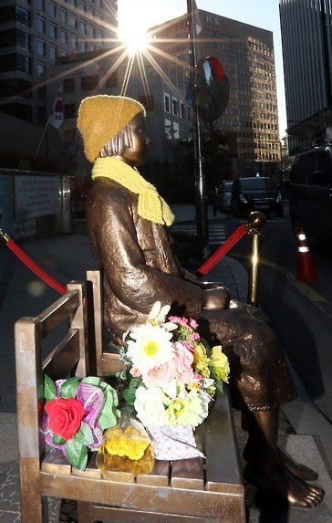 """A statue of a young girl, symbolizing the victims of Japan's sexual enslavement, is seen in this photo taken on Dec. 28, 2015. The statue, set up in front of the Japanese embassy in Seoul, has become an issue in the agreement announced on the day by South Korea and Japan to end their confrontation over """"comfort women."""" Japan is pressing for it to be relocated elsewhere, and South Korea said it will take into account Japan's concerns and try to solve the situation in an appropriate manner. (Yonhap)"""