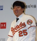 Kim Hyun-soo, an outfielder who is moving on to the Baltimore Orioles, poses in his new team's uniform at a news conference in Seoul on Dec. 29, 2015. Kim, 27, signed a two-year contract amounting to US$7 million with the major league team and became the first South Korean player to jump from the Korea Baseball Organization to the Major League Baseball via free agency. (Yonhap)