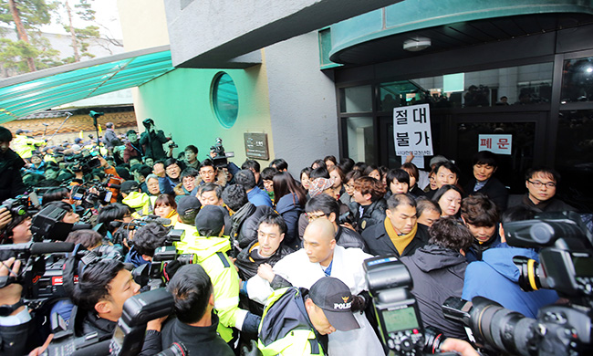 Police officers try to forcibly remove temple officials from the entrance of a building on the grounds of Jogye Temple in central Seoul, Wednesday, where Korean Confederation of Trade Unions (KCTU) head Han Sang-gyun has taken refuge to avoid arrest. (Yonhap)