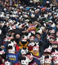 South Korean protesters attend an anti-government rally in downtown Seoul, South Korea, Saturday, Dec. 5, 2015. Wearing white half-masks and carrying flowers and banners, thousands of South Koreans marched in Seoul on Saturday against conservative President Park Geun-hye, who had compared masked protesters to terrorists after clashes with police broke out at a rally last month. (AP Photo/Ahn Young-joon)