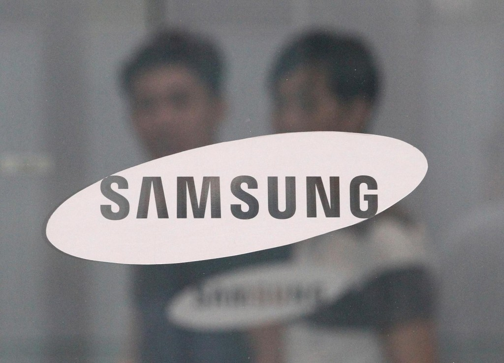 In this July 17, 2015 file photo, employees walk past a logo of Samsung Group at the head office of Samsung C&T Corp. in Seoul, South Korea. South Korea's financial regulator said Friday, Dec. 4, 2015 it has launched an investigation into possible insider trading by Samsung executives related to a contentious takeover deal. (AP Photo/Ahn Young-joon, File)