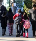 Parents take their children return home from school early Tuesday, Dec. 15, 2015, in Los Angeles. All schools in the vast Los Angeles Unified School District, the nation's second largest, have been ordered closed due to an electronic threat Tuesday. (AP Photo/Ringo H.W. Chiu)
