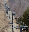 A chairlift sits idle at Oak Mountain Ski Center on Tuesday, Dec. 8, 2015, in Speculator, N.Y. Some Northeasterners are beginning to wonder if a white Christmas may just be a dream, and business owners who rely on snow are starting to worry if warm weather could lead to a nightmare winter. (AP Photo/Mike Groll)