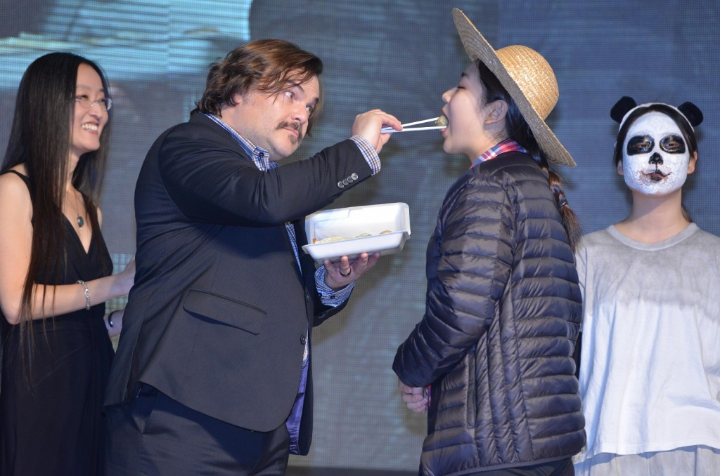 """Jack Black playfully feeds a fan, while Jennifer Yuh, left, the Korea-born director of the """"Kung Fu Panda 3,"""" laughs. (Newsis)"""