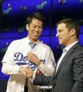 Newly signed Los Angeles Dodgers pitcher Kenta Maeda, from Japan, is introduced by Andrew Friedman, the team's president of baseball operations, at a news conference in Los Angeles on Thursday, Jan. 7, 2016. Maeda, 27, signed an eight-year contract with the baseball club that guarantees the right-hander $25 million, but he can earn over $100 million during the length of the deal if he meets all performance incentives. (AP Photo/Nick Ut)