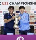 Shin Tae-yong (R), head coach of the South Korean men's under-23 football team, and Makoto Teguramori, his Japanese counterpart, hoist the champion's trophy for the Asian Football Confederation (AFC) U-23 Championship during their press conference in Doha on Jan. 29, 2016. (Yonhap)