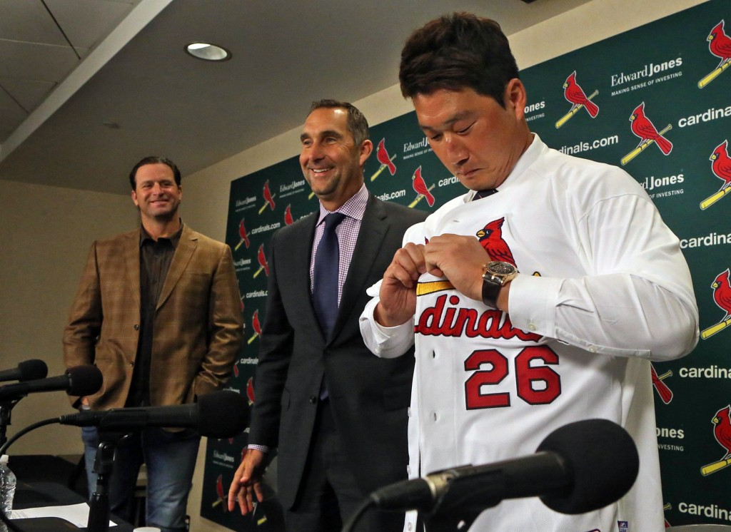 New St. Louis Cardinals relief pitcher Seung-Hwan Oh puts on his new jersey on Monday, Jan. 11, 2016, during a news conference as Cardinals manager Mike Matheny, left, and Senior Vice President and General Manager John Mozeliak look on, at Busch Stadium, in St. Louis. (J.B. Forbes/St. Louis Post-Dispatch via AP)