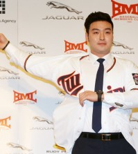 Park Byung-ho puts on the Minnesota Twins uniform at a press conference in the Grand Hilton Seoul Hotel, Thursday. (Yonhap)