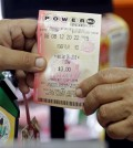 A clerk hands over a Powerball ticket to a customer, Wednesday, Jan. 6, 2016, at a local grocery store in Hialeah, Fla. The estimated Powerball jackpot for Wednesday night has soared to $500 million. The last time Powerball had grown this large was in February 2015, when three winners split a $564.1 million prize. (AP Photo/Alan Diaz)