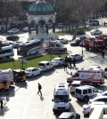 """Ambulances and firefighters stationed near the city's landmark Sultan Ahmed Mosque or Blue Mosque after an explosion at Istanbul's historic Sultanahmet district, which is popular with tourists, Tuesday, Jan. 12, 2016. The Istanbul governor's office says the explosion at the city's historic Sultanahmet district has killed least 10 people. A statement says 15 other people were injured in Tuesday's blast. The cause of the explosion is under investigation, but state-run TRT television says it was likely caused by a suicide bomber. The monument in the background is """"German Fountain."""" (IHA via AP) TURKEY OUT"""