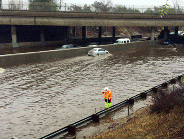 In this photo provided by the California Department of Transportation, a Caltrans worker probes for a drain in standing water that closed down most lanes of both sides of Interstate 5, the Golden State Freeway, in the Sun Valley area of Los Angeles' San Fernando Valley Wednesday, Jan. 6, 2016. El Nino storms left several inches of rain and snow throughout California, with more precipitation expected later in the week.(Jeremy Theisgen/California Department of Transportation via AP)
