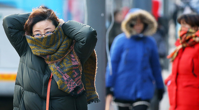 A woman wraps a muffler around herself in central Seoul, Monday, when the morning temperature fell to minus 6 degrees Celsius. The temperature is forecast to fall to minus 14 degrees Tuesday morning, and to stay below zero throughout the day. ( Yonhap)
