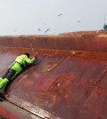 A Coast Guard rescuer tries to enter a capsized Chinese fishing boat off South Korea's southwestern coast on Jan. 27, 2016, to save crew members trapped inside. The vessel overturned hile it was being towed by another Chinese fishing boat. There were 10 fishermen aboard the boat. (Photo courtesy of West Sea Fisheries Management Service) (Yonhap)