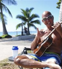 "In this photo taken Tuesday Jan. 26, 2016, Kent Terada shows the shaka or ""hang loose"" sign while sitting at Ala Moana Beach Park in Honolulu. A new study looking at the five elements of a well ordered life, such as financial security, sense of community and purpose, ranks Hawaii just ahead of Alaska. (AP Photo/Audrey McAvoy)"