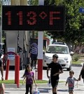 FILE - Pedestrians walk past a digital thermometer reading 113 degrees Fahrenheit in the Canoga Park section of Los Angeles on Saturday, Aug. 15, 2015. The National Weather Service issued warnings of excessive heat throughout Southern California into Saturday night, with some areas expected to see highs of 10 to 15 degrees above normal. (AP Photo/Richard Vogel)