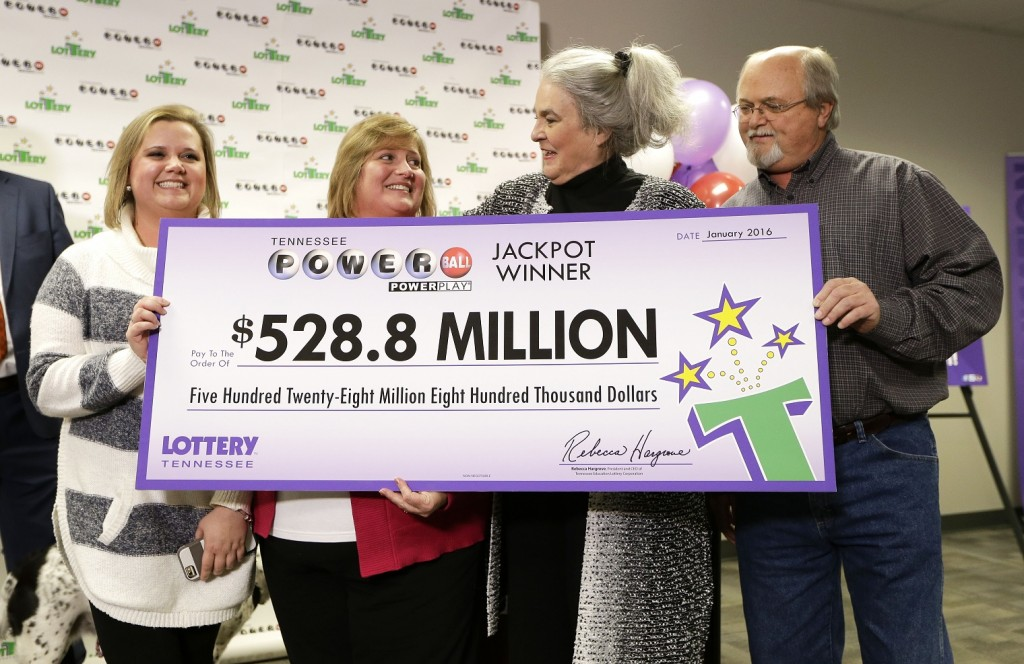 Rebecca Hargrove, second from right, president and CEO of the Tennessee Lottery, presents a ceremonial check to John Robinson, right; his wife, Lisa, second from left; and their daughter, Tiffany, left; after the Robinson's winning Powerball ticket was authenticated at the Tennessee Lottery headquarters Friday, Jan. 15, 2016, in Nashville, Tenn. The ticket was one of three winning tickets in the $1.6 billion jackpot drawing. (AP Photo/Mark Humphrey)