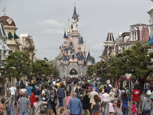 FILE - This Tuesday, May 12, 2015 file photo shows visitors walking toward the Sleeping Beauty's Castle, background, at Disneyland Paris in Marne la Vallee, east of Paris, France. A French police official says a man found to be carrying two handguns has been arrested at a hotel at Disneyland Paris. France remains under a state of emergency since Nov. 13 Islamic extremist attacks around Paris that killed 130 people. (AP Photo/Michel Euler, File)