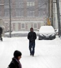 Pedestrians walk along First Street South as snow falls, Friday, Jan. 22, 2016, in Charlottesville, Va.  (Ryan M. Kelly/The Daily Progress via AP)