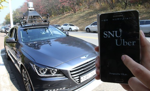 """An IT research team at Seoul National University shows off """"SNUber,"""" an automated, driverless cab that can be hailed and maneuvered using a smartphone app, at university campus in Seoul on Nov. 4, 2015. The vehicle operates on a preloaded 3-D map, with cameras and sensors detecting surroundings up to 80 meters in front and back. (Yonhap)"""