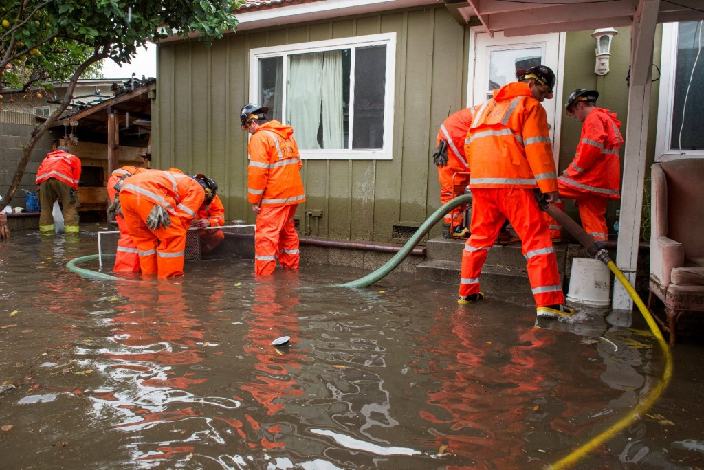 Orange County Fire Authority firefighters work to pump out flood waters from a home in Santa Ana, Calif., Wednesday, Jan. 6, 2016. El Nino storms lined up in the Pacific, promising to drench parts of the West for more than two weeks and increasing fears of mudslides and flash floods in regions stripped bare by wildfires. (Leonard Ortiz/The Orange County Register via AP)