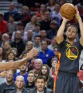 Golden State Warriors guard Stephen Curry, right, shoots over Portland Trail Blazers guard C.J. McCollum, left, during the first half of an NBA basketball game in Portland, Ore., Friday, Feb. 19, 2016. (AP Photo/Craig Mitchelldyer)