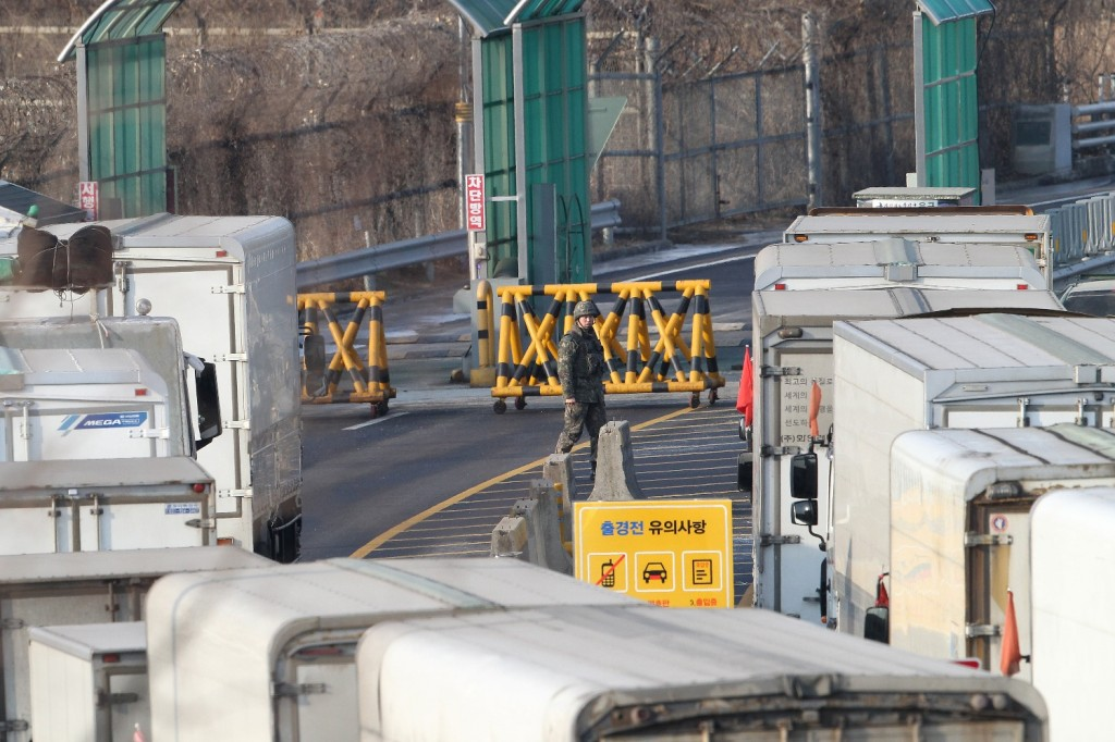 South Korean cargo trucks wait to head to the North Korean city of Kaesong as a South Korean Army patrols at the customs, immigration and quarantine office near the border village of Panmunjom in Paju, South Korea, Thursday, Feb. 11, 2016. South Korea said Wednesday that it will shut down a joint industrial park with North Korea in response to its recent rocket launch, accusing the North of using hard currency from the park to develop its nuclear and missile programs. (AP Photo/Ahn Young-joon)