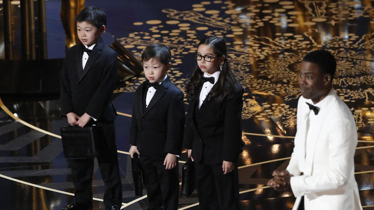 Oscars host Chris Rock, right, introduces three Asian children as Price Waterhouse representatives during a controversial spoof at the 88th Academy Awards. (Robert Gauthier / Los Angeles Times)