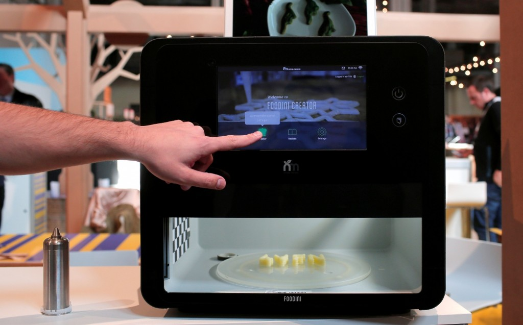"A man touches the screen of a 3-D food printer during the Mobile World Congress wireless show in Barcelona, Spain, Tuesday, Feb. 23, 2016. Natural Machines co-founder Lynette Kucsma insisted her company hadn't replicated Star Trek's ""food synthesizer"" that made munchies appear at Captain Kirk's mere command. But they sure have come pretty close with their 3-D food printer. (AP Photo/Manu Fernandez)"