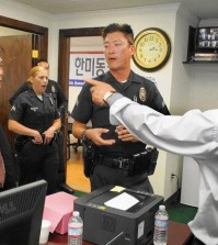 With police officers looking on, Sung Hoon Yoon, left, and Sung Woong Kim argue in the offices of the Korean American United Foundation in 2014. Yoon and Kim each claim to be the legitimate leader of the foundation. (Sang H. Park / The Korea Times Los Angeles)