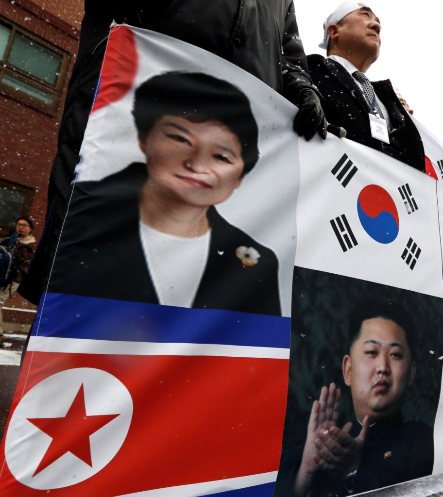 South Korean protesters hold a banner showing the pictures of South Korean President Park Geun-hye and flag, top and North Korean leader Kim Jong Un and flag, bottom, during a rally to support the President Park Geun-hye's policy about Kaesong industrial park in Seoul, South Korea, Tuesday, Feb. 16, 2016. (AP Photo/Lee Jin-man)