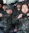 Saenuri Party Chairman Kim Moo-sung, right, listens to the commander of the 6th Infantry Division during his visit to a general post near the border in Cheorwon County, Monday. (Joint press corps)