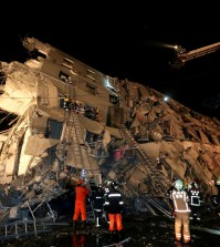 Rescue workers search a toppled building after an earthquake in Tainan, Taiwan, Saturday, Feb. 6, 2016. The 6.4-magnitude earthquake struck southern Taiwan early Saturday, toppling at least one high-rise residential building and trapping people inside. Firefighters rushed to pull out survivors. (AP Photo)