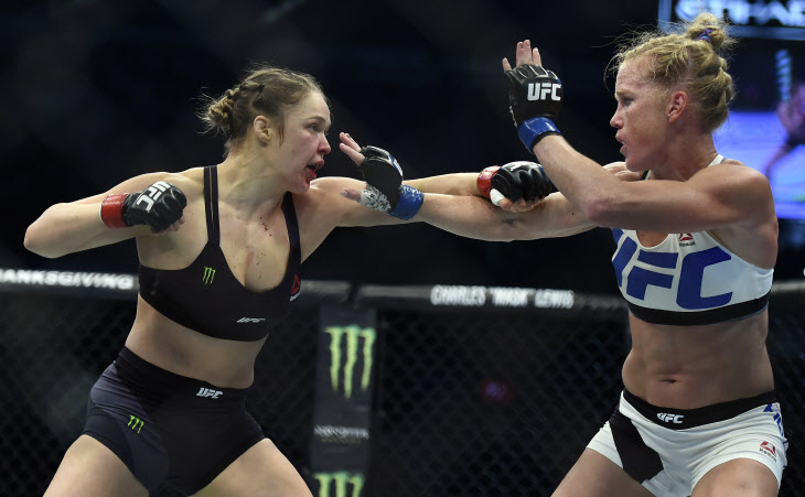 FILE - In this Sunday, Nov. 15, 2015 file photo, Ronda Rousey, left, and Holly Holm fight during their UFC 193 bantamweight title bout in Melbourne, Australia. Holm pulled off a stunning upset victory over Rousey in the fight, knocking out the women's bantamweight champion in the second round with a powerful kick to the head Sunday. Ronda Rousey says she had dark thoughts after she lost her bantamweight title to Holly Holm in Australia last year, her first defeat since joining UFC, Tuesday, Feb. 16, 2016. (AP Photo/Andy Brownbill, File)