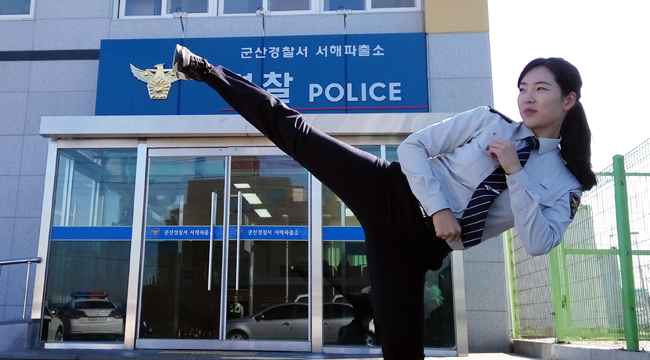Kim Seung-hee, a former national taekwondo champion turned police officer, demonstrates a side kick in front of her office in Gunsan, North Jeolla Province, Thursday. (Yonhap)
