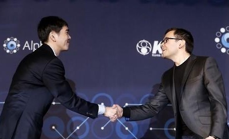 South Korean Go player Lee Se-dol (L) shakes hands with Google DeepMind CEO Demis Hassabis at their post-match press conference at Four Seasons Hotel in Seoul on March 15, 2016. Lee played Go matches against AlphaGo, an artificial intelligence program developed by Google DeepMind. (Yonhap).