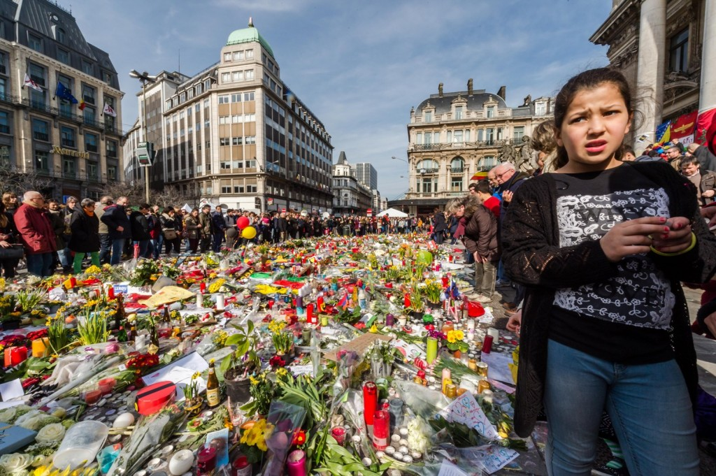 People stop and look at floral tributes at a memorial site at the Place de la Bourse in Brussels, Saturday, March 26, 2016. Brussels airport officials say flights won't resume before Tuesday as they assess the damage caused by twin explosions in the terminal earlier this week. (AP Photo/Geert Vanden Wijngaert)