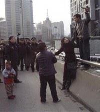 In this Dec. 8, 2006 photo, Pu Zhengxing, right, a carpenter trying to get back his unpaid wage of 3,000 yuan, takes hostage the wife of his foreman in Xi'an of China's Shaanxi province. Policemen eventually saved the hostage and arrested Pu. Wage arrears are a major problem for Chinese laborers, especially migrants working on casual terms in the construction industry. (Color China Photo via AP)