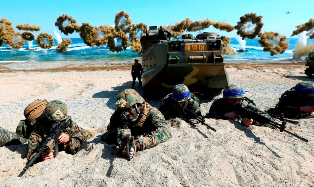 FILE - In this March 12, 2016 file photo, U.S. Marines, left, and South Korean Marines, wearing blue headbands on their helmets, take positions after landing on the beach during the joint military combined amphibious exercise, called Ssangyong, part of the Key Resolve and Foal Eagle military exercises, in Pohang, South Korea. It's a demand North Korea has been making for decades: The U.S. and South Korea must immediately suspend their annual military exercises if they want peace on the Korean Peninsula. And, once again, it's a demand that is falling on deaf ears. This year's exercises are bigger than ever before and reportedly include training to take out Kim Jong Un himself. For Pyongyang's ruling regime, that's a bridge too far. But probably not far enough to fire the first shots over. (Kim Jun-bum/Yonhap via AP, File)