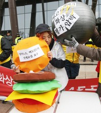 """Members of the Arbeit Workers Union, representing part-time workers, stage a performance urging McDonald's Korea to scrap its """"45 second rule"""" on making burgers, among other demands, in front of the fast food chain's office in Gwanghwamun, downtown Seoul, Monday. The union called for a collective bargaining session with the company on the issues. (Yonhap)"""