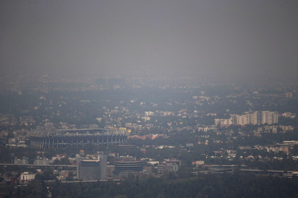 Mexico City's Azteca Stadium, left, is seen through a thick haze, Tuesday, March 15, 2016. The Mexico City government declared its first air pollution alert in 11 years Monday, after ozone levels reached almost twice the acceptable limit. (AP Photo/Eduardo Verdugo)
